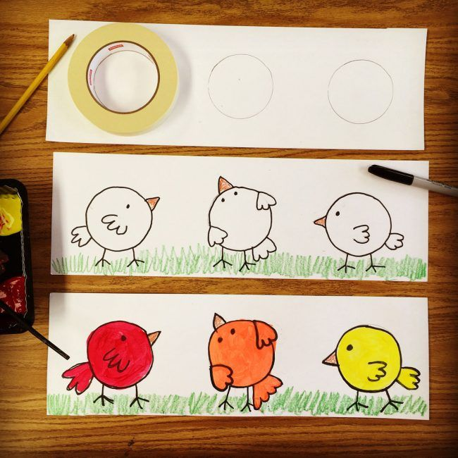 """This is one of my 'keeper"""" kinder projects, so much more fun than painting a boring color wheel. Materials: • 12″ x 18″ Drawing paper, cut to 6″ x 18″ • Masking tape rolls • Crayons • Black Sharpie, fine tip • Tempera paint Give students wide sheet of paper as shown. Have them first trace … Read More"""