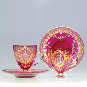 Humler & Nolan | June 2011  Pair of liqueur caups and saucers attributed to Moser. The cranberry glass ornately enameled with 18th century figures surrounded by colorful floral swags and golden scrolls