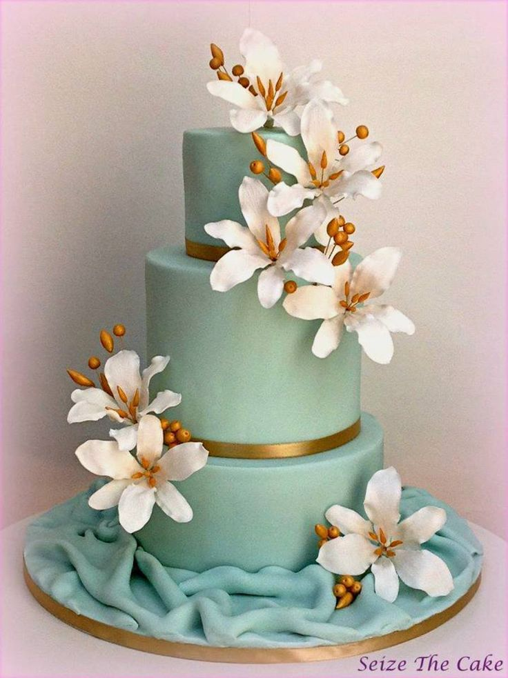 Wedding cake with sugar lilies and gold details.