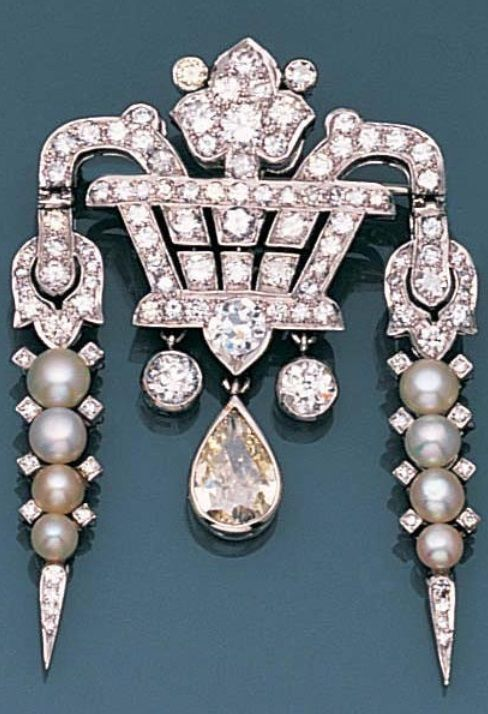 An Art Deco diamond and seed pearl giardinetto brooch, circa 1925. The highly stylised basket of flowers set with single and brilliant-cut diamonds, issuing two seed pearl pampilles, with a central pear-shaped diamond drop, principal diamond approximately 0.60 carat, length 4.5cm. #ArtDeco #brooch