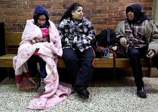 Marquetta Gilmore (left), 14, Nantalia Torres, 17, and Terry Goins warm up in the lobby of Riverside University High School in Milwaukee on Friday after sleeping outside overnight. Goins, a safety aid, stayed out all night with a group of more than 24 students who participated in the 13th annual 'Box City' at Riverside to raise money for Habitat Humanity and bring awareness to homelessness. - Image credit: Kristyna Wentz-Graff