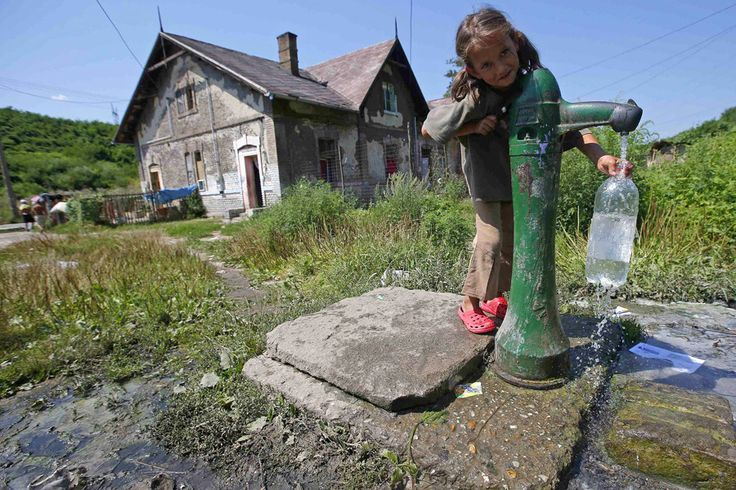 A Roma girl fills up a plastic bottle from a public well at the impoverished outskirts of Ozd, northeastern Hungary