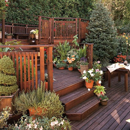 Attractive Sloped garden ideas. Grand multilevel deck with planted containers galore!