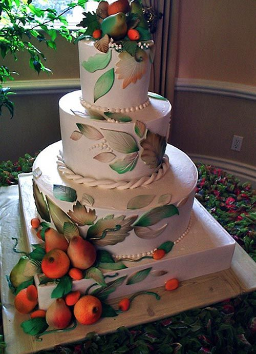 Huge, round, four tier Fall themed wedding cake decorated with edible hand crafted fondant leaves and airbrushed white chocolate fruit