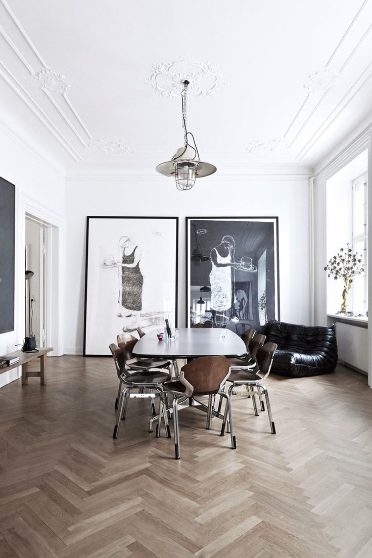 Antique home with lots of artwork and herringbone wood floors, white walls and minimalist design