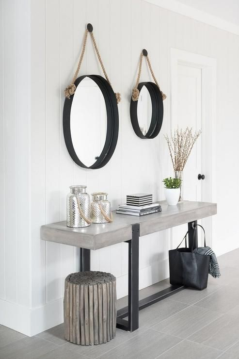 Two captain's hanging mirrors stand over a concrete console table alongside a gray wash floor.