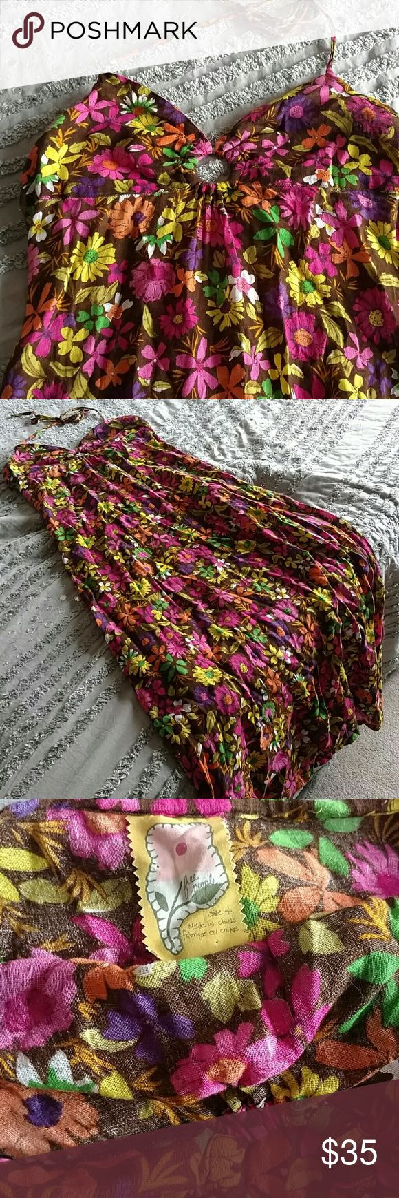 """Free People Summer Flower Maxi Dress Maxi dress by Free People. Made of a soft gauzy cotton. I am 5'5"""" and this maxi dress hits the ground perfectly in flat sandals. The base color is brown with multiple color flowers. The chest is double lined, the top ties around neck and in back. It has a very low back with elastic. There is no zipper. Size is 4. I would say it's a small to medium. It's a little big in the cheat for me. I wore it to a music festival VIP event and got many compliments…"""