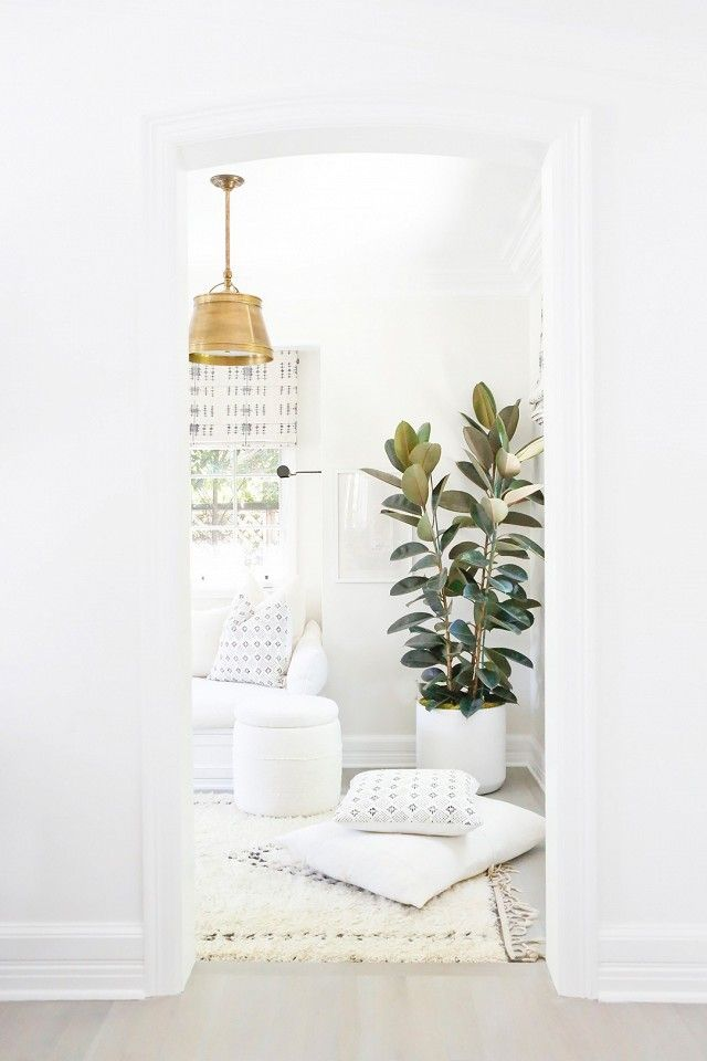 Erin Fetherston's all-white living space with a Morrocean area rug, a white sofa, and a gold pendant light