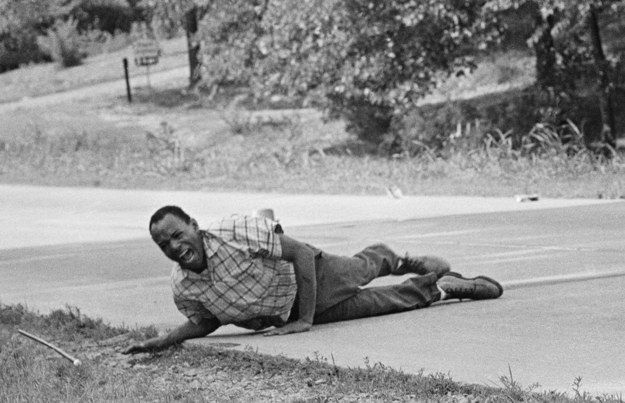 Civil rights activist James Meredith grimaces in pain as he pulls himself across Highway 51 after being shot in Hernando, Mississippi, on June 6, 1966. Meredith, who defied segregation to enroll at the University of Mississippi in 1962, completed his protest march from Memphis, Tennessee, to Jackson, Mississippi, after receiving treatment for his wounds.