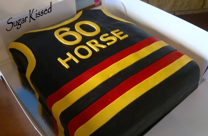An Adelaide Crows Football themed Guernsey cake created by Shandi Sansom from Sugar Kissed. Features personalisation of name and age. Please visit my facebook page to see more of my work: www.facebook.com/sugarkissedshandi