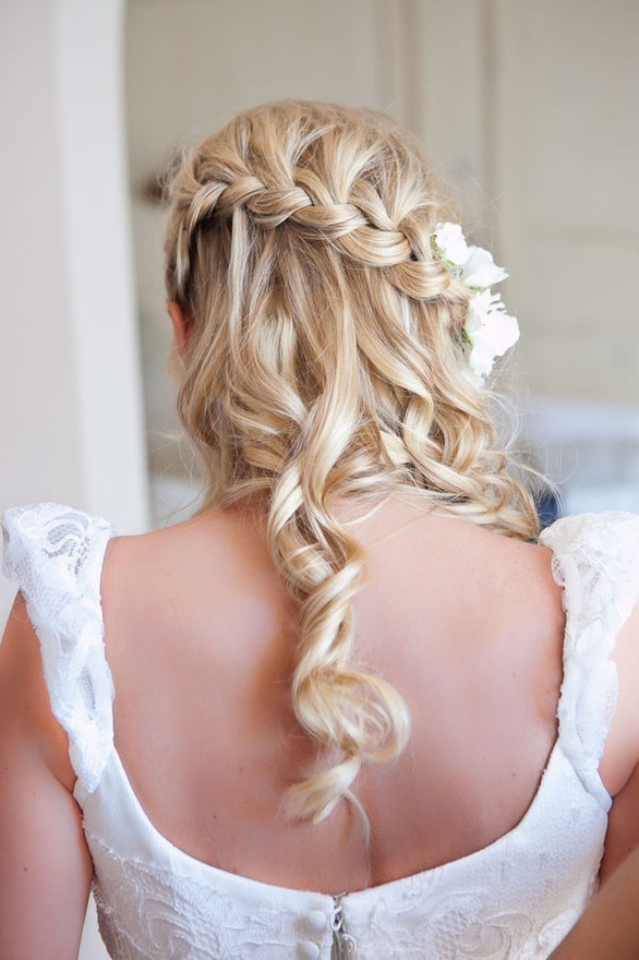 A beautiful wedding hairstyle. Hair with curls, a braid and white flowers. Very romantic! Hair-of-marriage