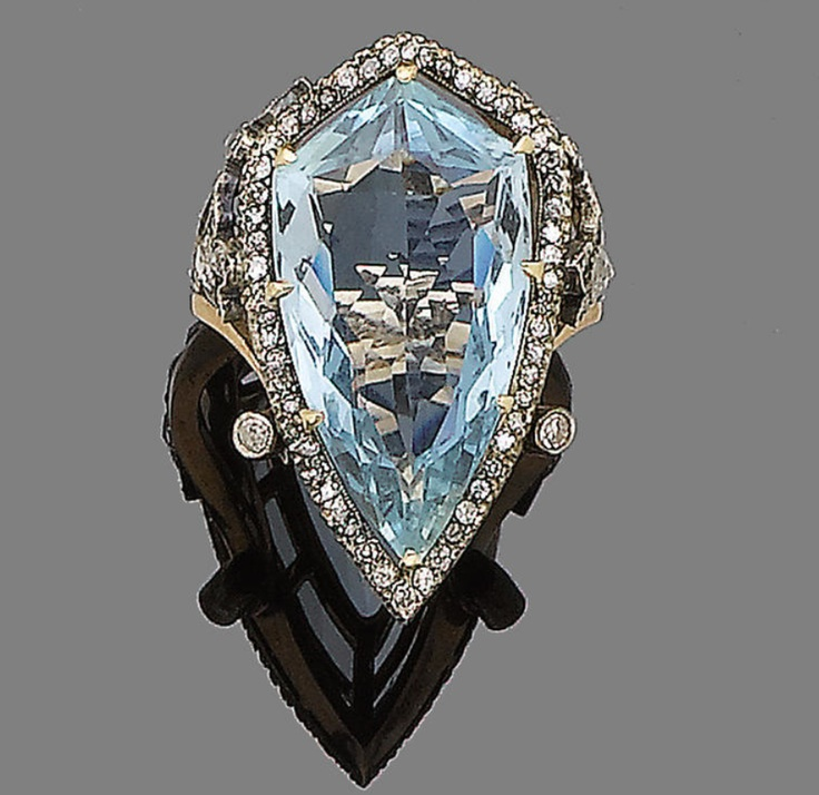 An aquamarine and diamond dress ring  The shield-shaped aquamarine within an openwork single-cut diamond surround, between tri-furcated rose-cut diamond shoulders, Russian assay marks. Edwardian or Edwardian style.