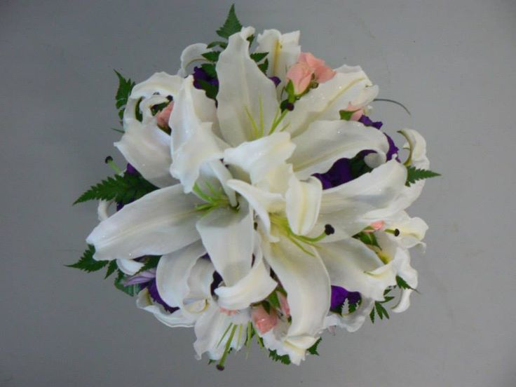 White oriental lilies, pale pink spray roses & purple lisianthus touched with a silver glitter spray
