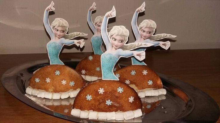 Elsa eierkoek Frozen traktatie werkwijze: snij eierkoek door de helft. Besmeer met witte chocopasta en plak tegenelkaar aan. Smeer op de onderom nog wat chocopasta en plak daar mini marshmallows tegenaan. Plak de suikerfiguur sneeuwsterretjes met wat poedersuiker en water op. Print een mooie Elsa uit en plak deze op een cocktailprikker en steek deze bovenin. #Frozen #Birthday #Party #Elsa #treat #tratar