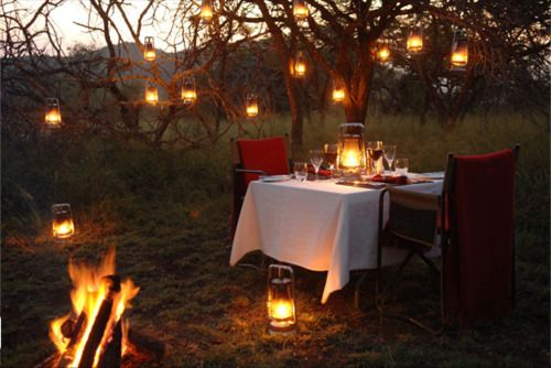 Magical outdoor eating area by bonfire and lantern glow.