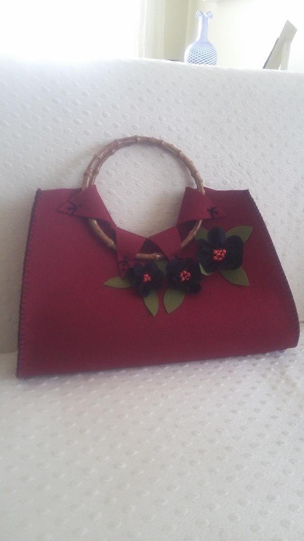 Fark yaratmak isteyen bayanlar için şık ve kullanışlı keçe çantalar.  Bordoya yakın Kırmızı çanta, yaklaşık 40x30x10 cm (UzunlukxYükseklikxDerinlik) ebatındadır.  Gri-lacivert-siyah renklerinde de mevcuttur.   İstenilen renklerde ve süsleme şekilleriyle zevkinize göre yapılır. Sipariş esnasında tedarik edilen malzeme renklerinde ton farkı olabilir.   Ebatın daha da büyük istenmesi, ahşap kulp eklenmesi gibi durumlarda ücret değişmektedir. (Yaklaşık 5 TL daha Fiat artar.)  Ürünün hazırlanma…