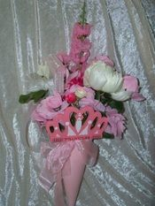 "Princess Themed Cemetery Flowers.  Pink and white- all feminine for the young or older person.  Has a painted wooden crown attached proclaiming ""princess"".  Pays tribute to anyone that truly shined."