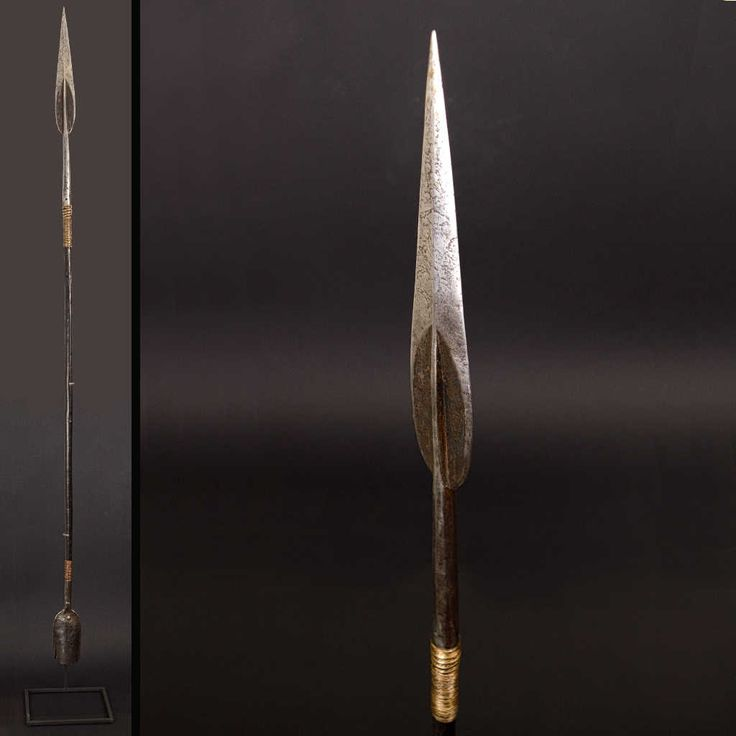 Ceremonial spear with leafy tip, wooden pole with a beautiful patina of use, enriched with brass rings.  At the bottom end there is a bell shape with clapper in forged iron. Height: 156 cm. (168 cm with pedestal)