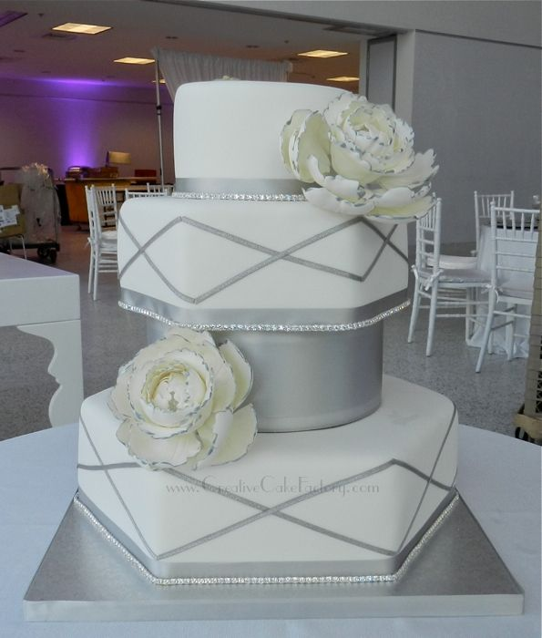 Silver & White Wedding Peony Cake - White wedding cake with hexagon & round tiers. Rhinestone banding and silver ribbons. Gumpaste Peonies with silver painted tips.