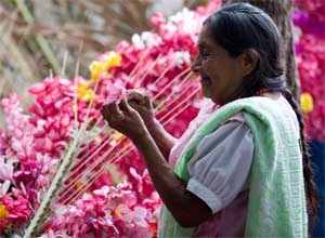 An indigenous woman creates a flower arrangement for a celebration, Panchimalco, El Salvador
