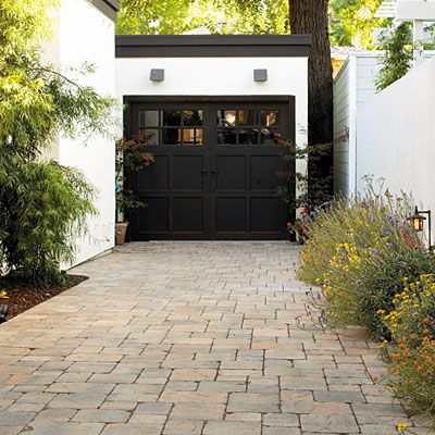 Concrete pavers line a driveway Durable concrete pavers set in a regular pattern are a good match for the architectural style of the house, and their subtly varied colors help mediate the starkness of a black-and-white color scheme.