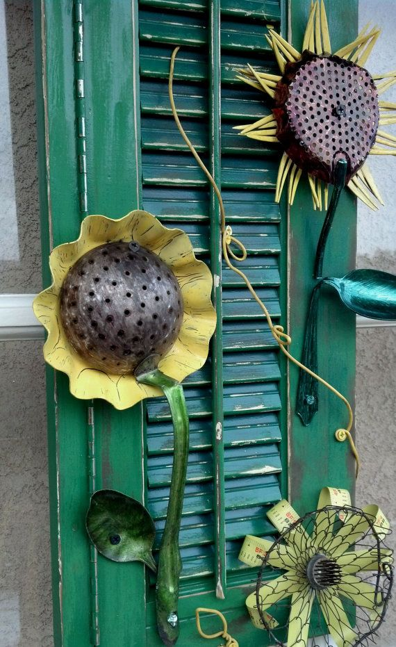 This rustic sunflower garden shutter art is created from salvaged parts and pieces. Great decoration for your garden wall or porch. The sunflowers are all made from various silverware, tart pans, garden parts, measuring tape and random found objects. The yellow vine is repurposed electrical wire and the green shutter came out of an old ice cream parlor window.  Back has wire hanger for easy installation. Note: Keep away from children, metal parts may be sharp.    Shutter measures: 10 x 32