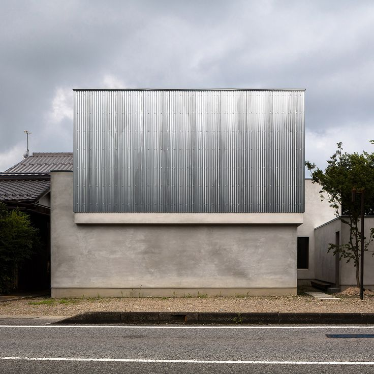 Sheets of corrugated steel envelop the upper storey of this house and studio for a photographer, which was designed by local architect Kouichi Kimura