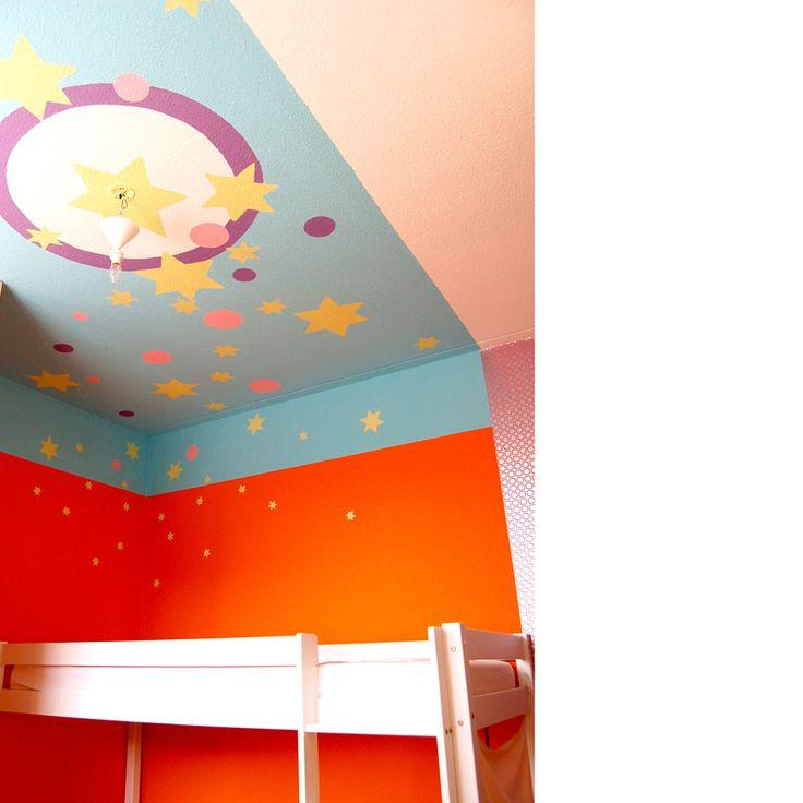 Wandschildering op plafond en muur van een meisjeskamer. De sterren dwarrelen naar haar bedje waar ze oplichten in 'glow in the dark'.  wandendoek.nl