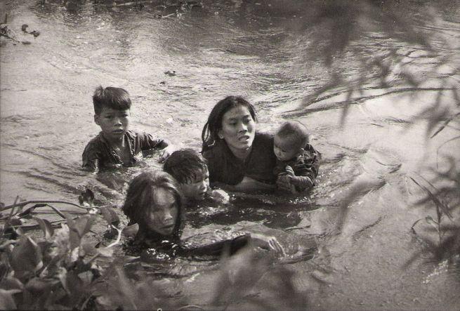 Sawada Kyoichi. 'Mother and children wade across river to escape U.S. bombing. Qui Nhon, South Vietnam' September 1965
