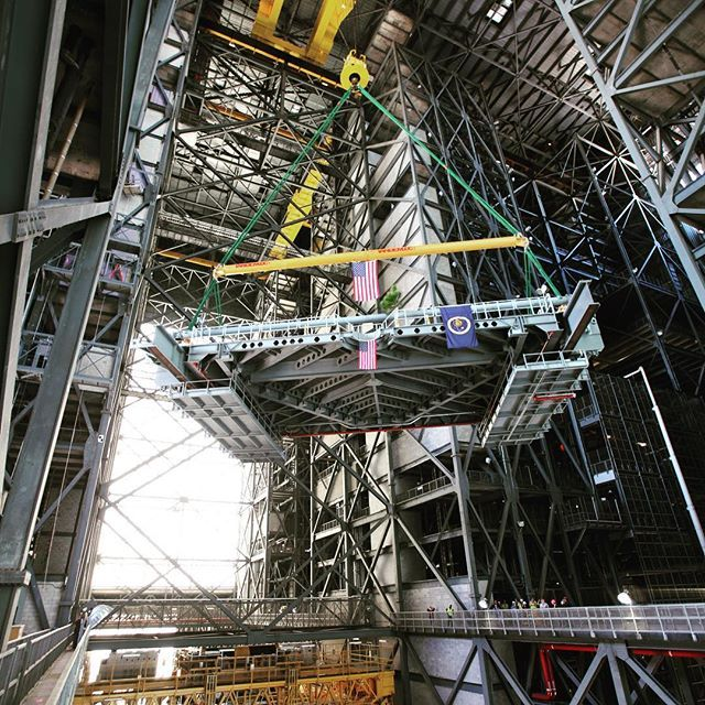 explorenasa High up in the transfer aisle of the Vehicle Assembly Building (VAB) at NASA's Kennedy Space Center in Florida, a crane turns the final work platform, A north, for transfer into High Bay 3. The platform will be installed and secured on its rail beam high up on the north wall of the high bay. The installation of the final topmost level completes the 10 levels of work platforms, 20 platform halves altogether, that will surround NASA's Space Launch System rocket and the Orion…