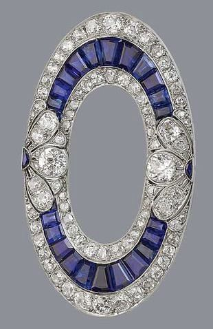 A sapphire and diamond brooch, circa 1915 The openwork ellipse set with calibré-cut sapphires, old brilliant and rose-cut diamonds, with additional pierced foliate decoration millegrain-set with similarly cut diamonds and crescent-shaped sapphires, diamonds approximately 3.40 carats total, width 5.3cm., cased by Hennell, Southampton St, London