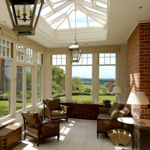 Orangery with floor-to-ceiling windows, a lantern-style roof and cream tiled floor