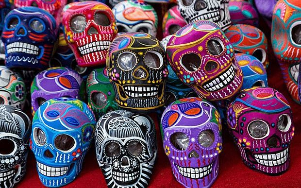 A vendor displays colorful painted skulls for the Day of the Dead festival at the Sunday market in Tlacolula de Matamoros, Mexico.
