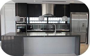 """Explore the bold statement of a black polytone finish with 60mm raven caesar stone bench tops and stainless steel appliances. This clean line kitchen has all the latest in blum soft close drawers,  integrated fridge and microwave, along with a stainless steel benchtop and 3D porcelain feature tile. """"A real inspirational Kitchen"""" by Zeev Kitchens.  #zeev #zeevkitchens #australianmade #madeinmelbourne #custommade #kitchens #cabinetmaker #essendon #springvale"""