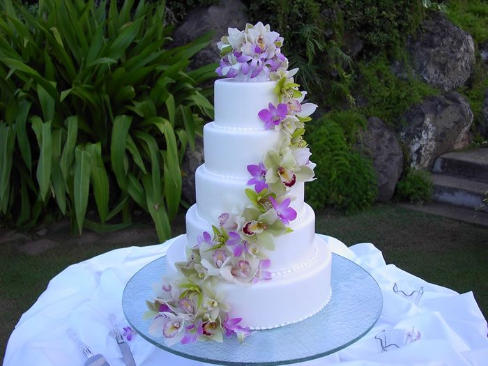 A trial of Orchid heads flowing down each layer of this 5 tier Wedding Cake.