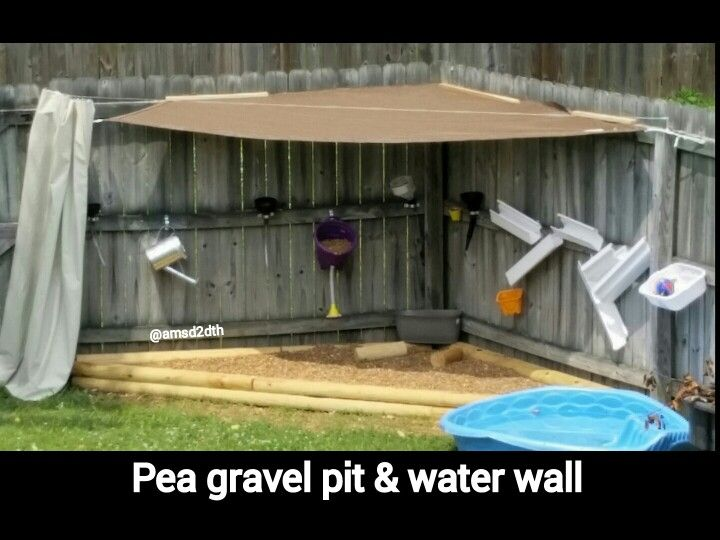 Pea gravel pit  water wall. My husband needs to finish the shade sail, but you get the idea. It only took one scoop ($20) of pea gravel to fill the area. I attached funnels, gutters,  buckets to the fence. We used the Ikea Dignitet curtain system to hold the heavy duty shower curtain liner for shade. My son and his friends have had a blast playing in the new area. ~@amsd2dth