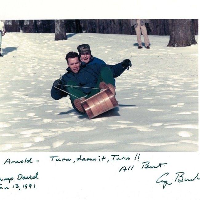 George H. Bush sledding with the future Governater of California, Arnold Schwarzenegger.