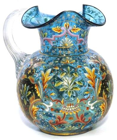 A Moser Prussian blue water pitcher, gold scrolling and polychrome flowers, applied crystal handle. Czechoslovakia, circa 1893-2007