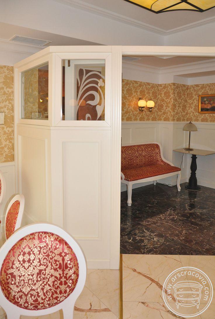 Wnętrze kawiarni w zabytkowej kamienicy, podzielone ścianką będącą kontynuacją okładzin ścian. Zabudowy stylizowane wykonane z lakierowanego mdf-u.