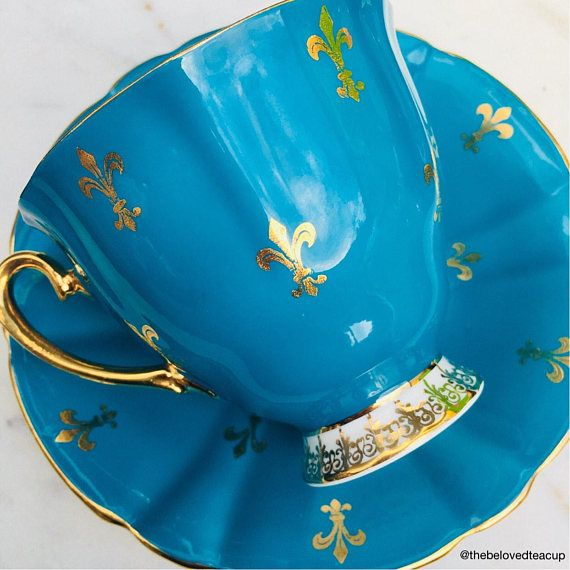 Stunning dark turquoise Windsor fleur de lis antique tea cup and saucer featuring vibrant orange and purple pansies. Set is in excellent antique condition with no chips, cracks or crazing and the paint/gold is still bright.