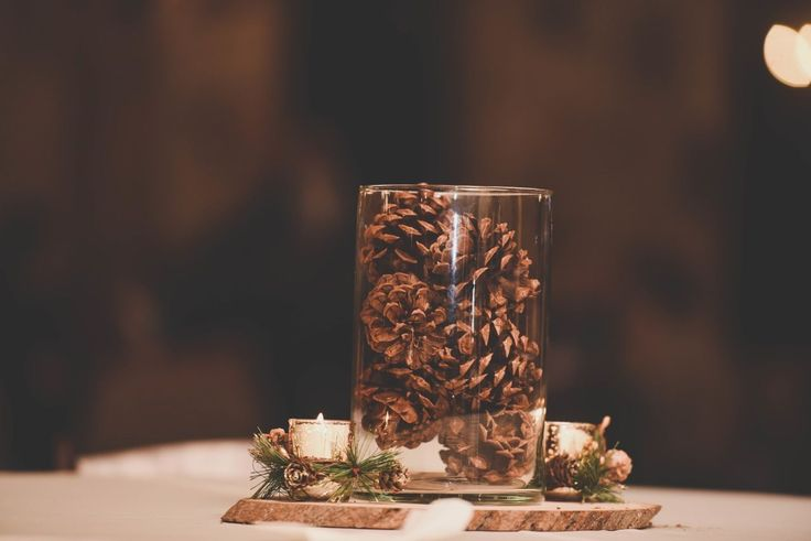 This pine cone wedding centerpiece is perfect for your winter wedding! Love the stump base, small candles surrounded by pine, and the pine cone vase at the center.  The perfect decor for your winter, Christmas, or December wedding! Photo taken at THE SPRINGS Event Venue.  Follow this pin to our website for more information, or to book your free tour! SPRINGS location:  The Lodge in Denton, TX Photographer:  April Pinto Photography #winterwedding #weddingdecor #weddingdecorations
