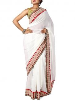 White with Red Ethnic Border Pure Chiffon Saree from Sayisha. A stylish designer saree with its simplicity lying in the Red border. The border features resham embroidery and gotta patti trim. Team with slender heels and embellished clutch for an elegant look. Blouse Piece is available with the saree & the blouse in the image is used only for photography.  Available on www.designerkapde.com