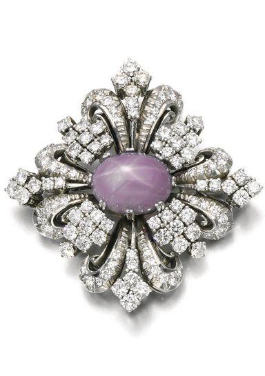 Star sapphire and diamond brooch Of scroll design, set with a purple star sapphire, brilliant- and single-cut diamonds.