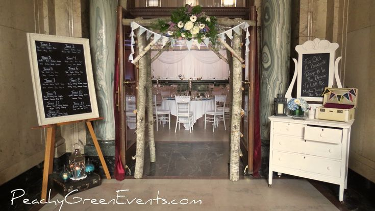 Vintage Dresser, Chalkboard Seating Chart and Rustic Birch Arch Wedding Entrance in Winnipeg's Historic Exchange District
