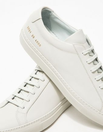 Low top sneaker from Woman by Common Projects in Off White. Heat pressed  gold serial number detail at lateral side.