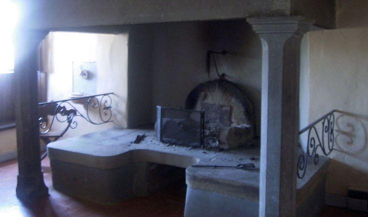A large fireplace supported by two original stone columns / Nel piano terreno si può ammirare un grande camino sostenuto da due colonne in pietra del 1500