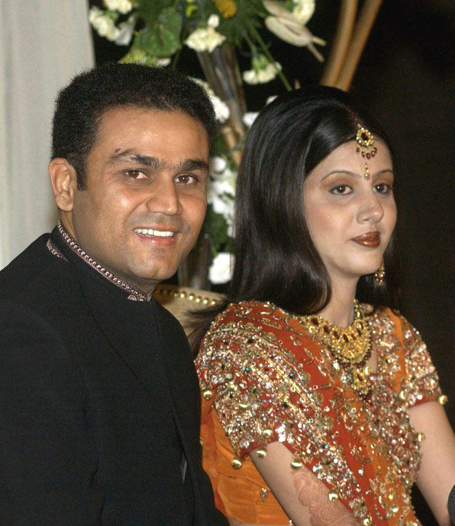 Virender Sehwag and new wife Aarti Ahlawat pose for photographers at their wedding reception in New Delhi. #Cricket