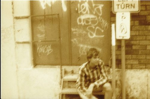 Lomography shot of brother posed near graffiti and near industrial sights. 35mm with Minolta x 570