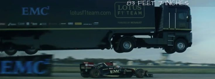 A Semi-Truck With Attached Trailer Jumps Over a Speeding Formula 1 Race Car