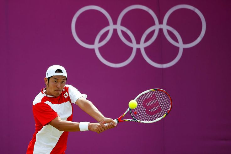 Tatsuma Ito of Japan returns a backhand shot to Milos Raonic of Canada in their fist round men's singles match at Wimbledon